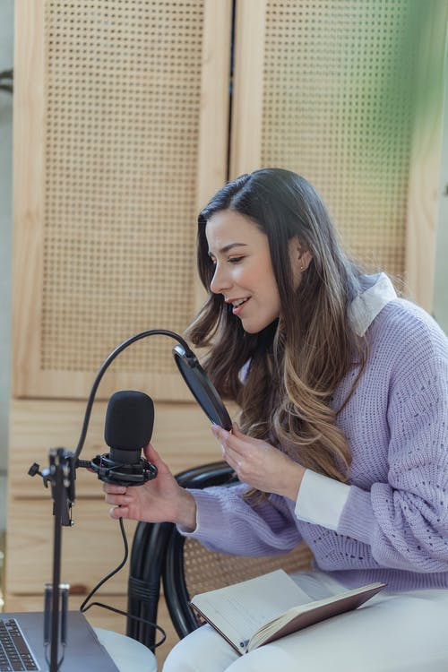 Young positive lady in casual clothes sitting in armchair while recording podcast on microphone with notepad on knees near laptop in light room