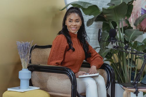 Black female in armchair with notepad near microphone in room