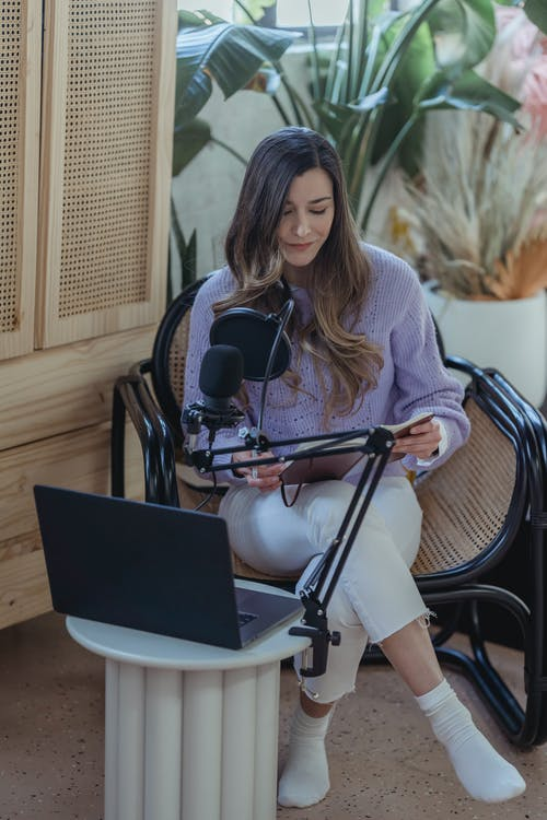High angle full body if female host sitting in armchair with crossed legs and recording audio on laptop with microphone