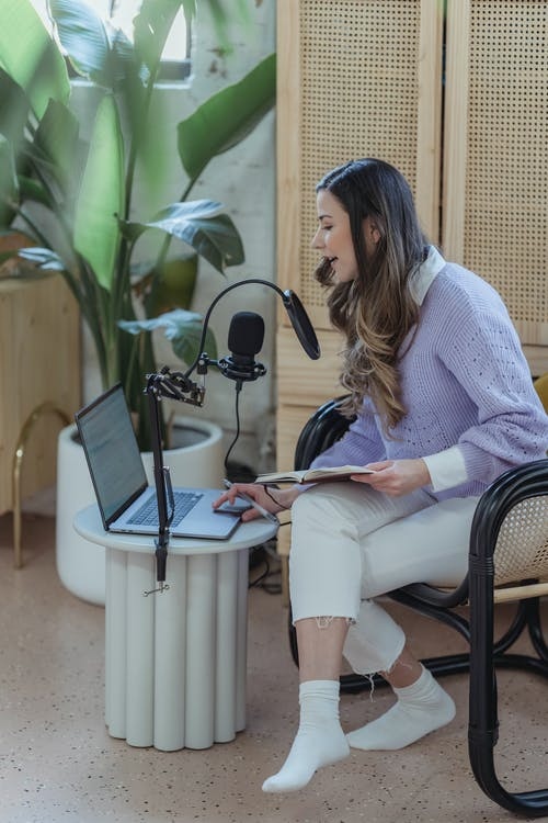 Female radio host broadcasting from home and using laptop
