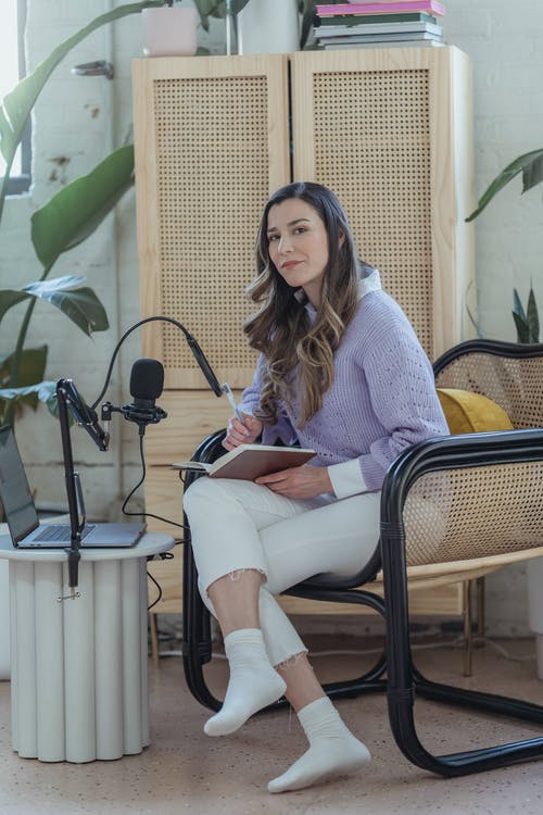 Full body of female sitting in armchair with notepad near laptop and microphone for remote broadcast