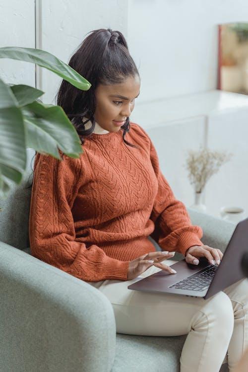 Focused black female freelancer doing online work on laptop