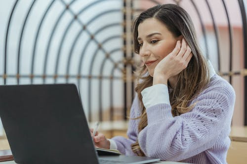 Smiling female teleworker leaning on hand while taking notes in planner during remote work at looking at screen