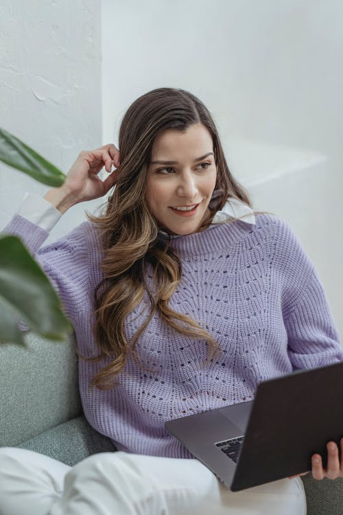 Young content female in knitted sweater with netbook sitting on couch while touching hair and looking away