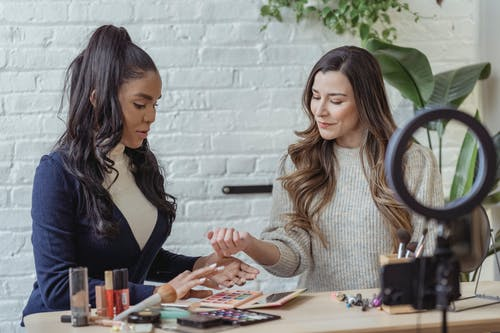 Young positive multiethnic female bloggers testing makeup products while sitting at table and recording vlog on smartphone placed on tripod with ring light