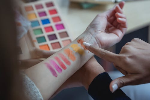 From above of crop unrecognizable young female makeup artist pointing at arm of client while applying colorful eyeshadows on wrist for testing