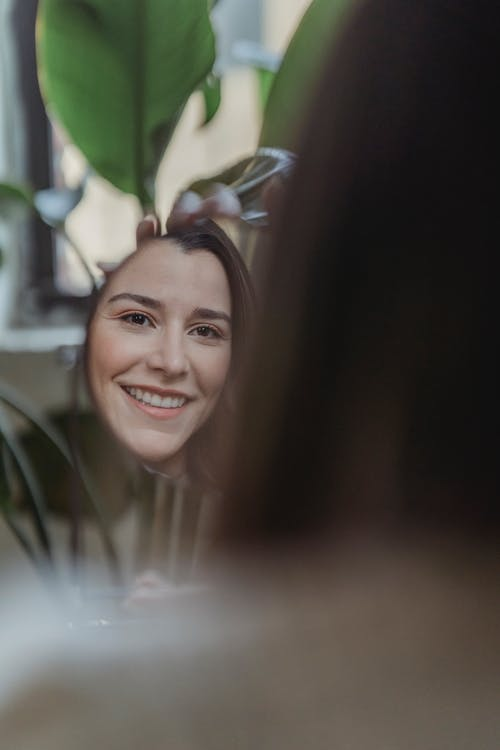 Confident young woman smiling and looking in round mirror