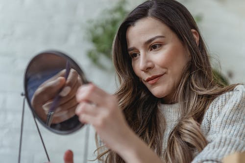 Graceful young female looking in mirror after doing makeup