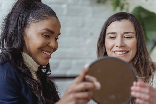 Happy young female client looking in mirror and smiling near positive ethnic makeup artist