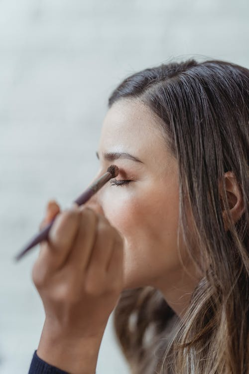 Side view of crop young female customer with ling brown hair and sitting in light studio closed eyes while anonymous makeup artist applying eyeshadows
