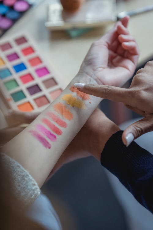 Unrecognizable ladies testing new palette of colorful eyeshadows