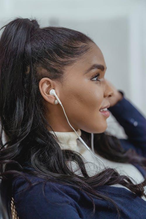Smiling young ethnic woman enjoying music in earphones