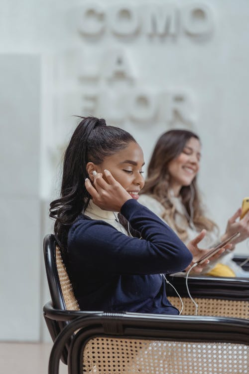 Cheerful young diverse female friends in earphone using smartphones in cafe
