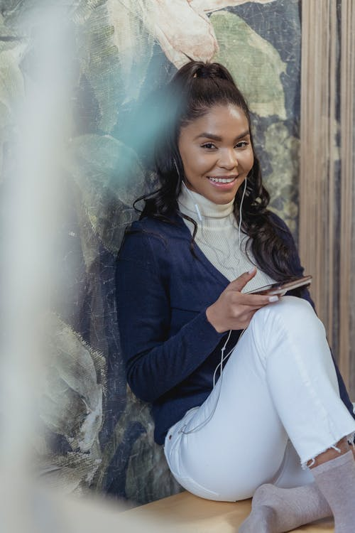 Cheerful young African American female with long dark hair in stylish outfit sitting on floor and home and smiling while using smartphone and listening to songs in earphones