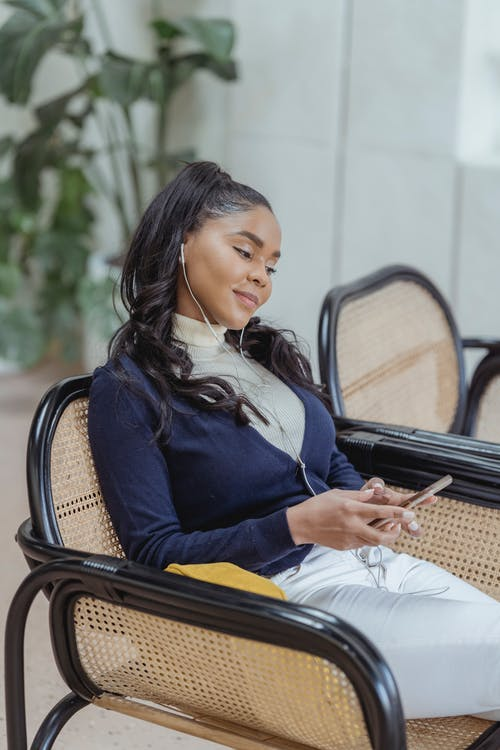 Happy young ethnic female with long dark hair in casual outfit relaxing in comfortable armchair and listening to favorite music in earphones via mobile phone