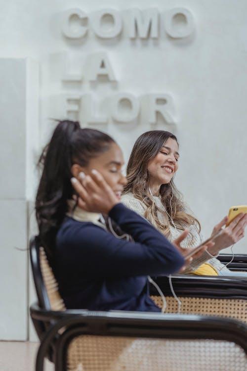 Happy young multiethnic in earphones speaking on mobile phones in workspace