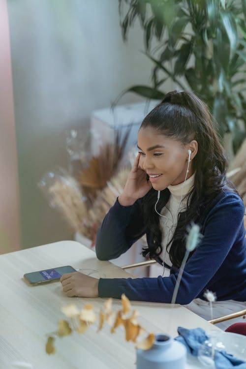 Delighted young black woman in earphones sitting at table and having phone call