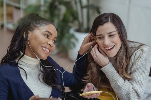 Happy young African American lady with smartphone and earphones smiling and sharing music with female best friend while chilling together in cozy cafe