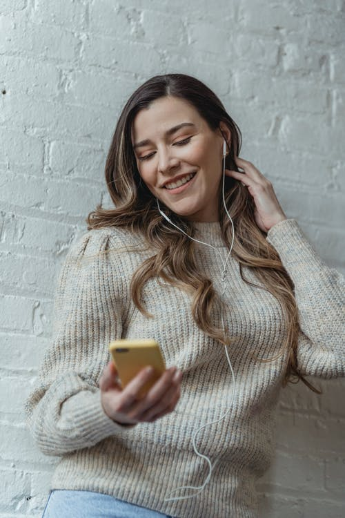Cheerful woman with earphones listening to music with smartphone