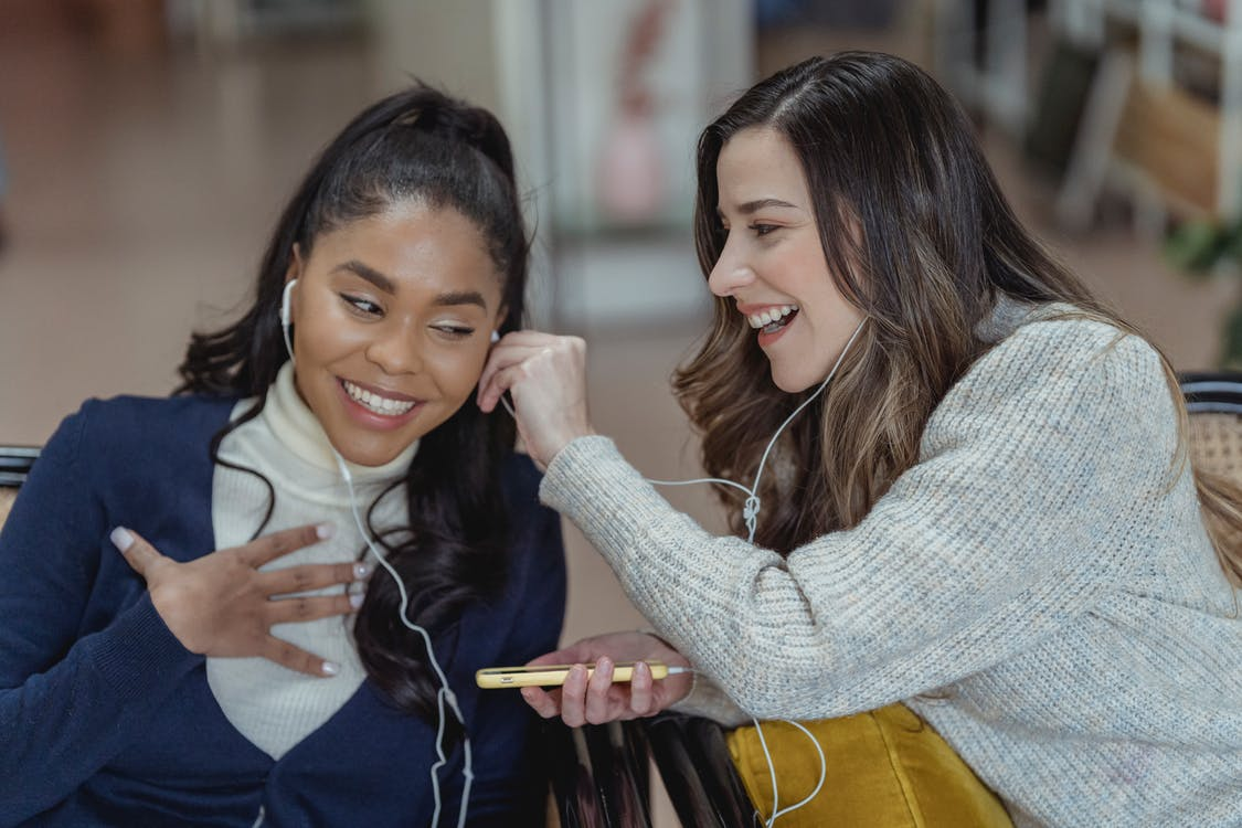 Multiracial cheerful women smiling and enjoying music in earphones while using mobile phone on blurred background