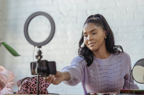 Glad African American female blogger with long dark hair using mobile phone and ring lamp while having video conversation online