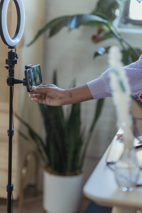 Black woman using smartphone on tripod with ring lamp
