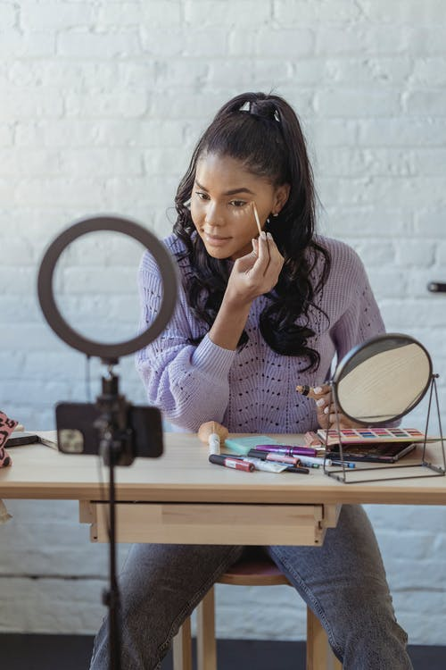 Young African American female blogger spreading foundation cream on face at table with cosmetics near smartphone recording video