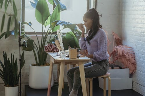 Side view of African American woman with long hair in trendy clothes sitting at table with cosmetics and applying makeup while filming vlog in light room