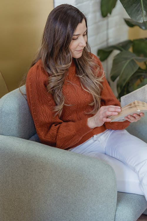 Concentrate woman with long hair in casual clothes sitting on armchair and reading interesting book in light room