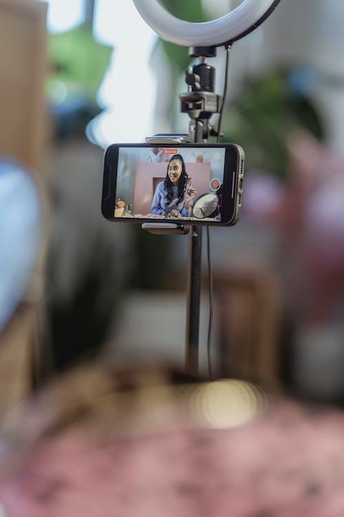 Black female filming beauty blog on smartphone