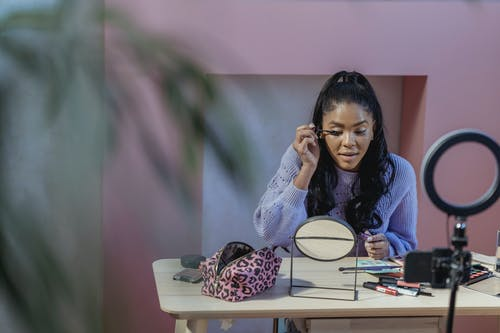 Calm African American woman blogger applying makeup and filming beauty blog on smartphone placed on tripod in room