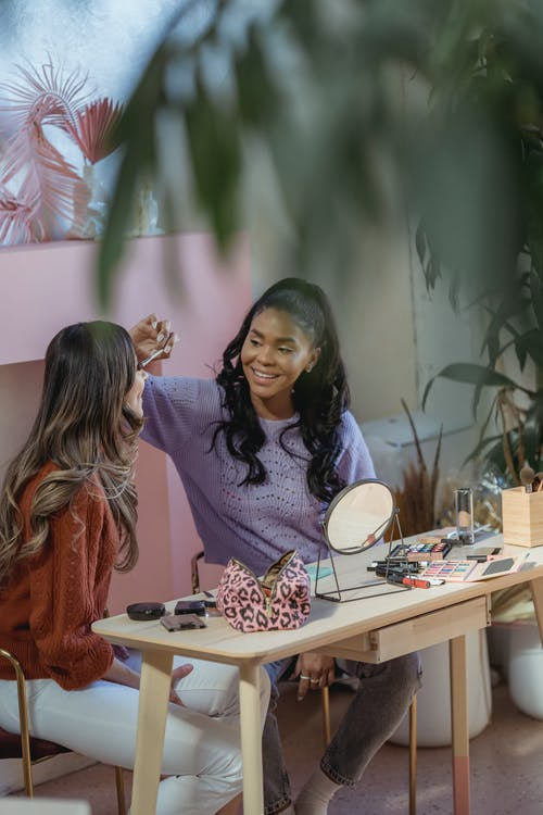 Cheerful black woman applying makeup on female friend
