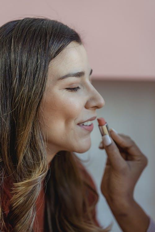 Crop visagiste applying lipstick on smiling model