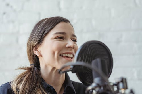 Positive female recording podcast on mic while working in light studio against white brick wall