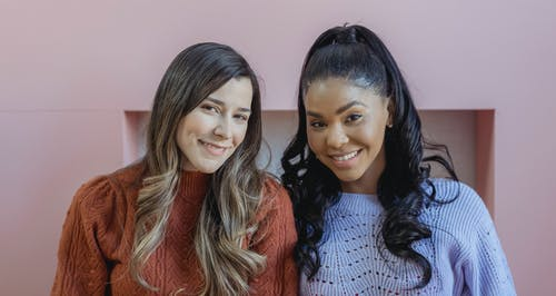 Positive multiracial female friends with long wavy hair and makeup smiling widely and looking at camera