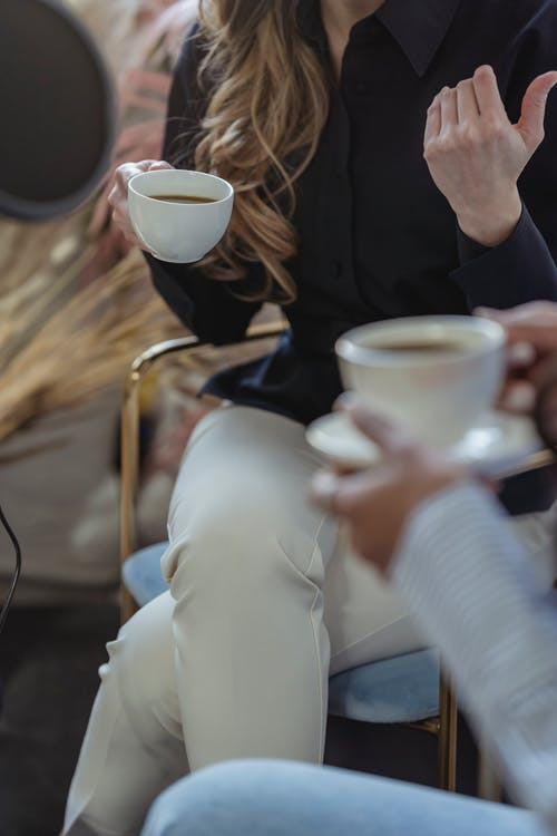 Crop anonymous female host talking to guest and having coffee while recording conversation on microphone