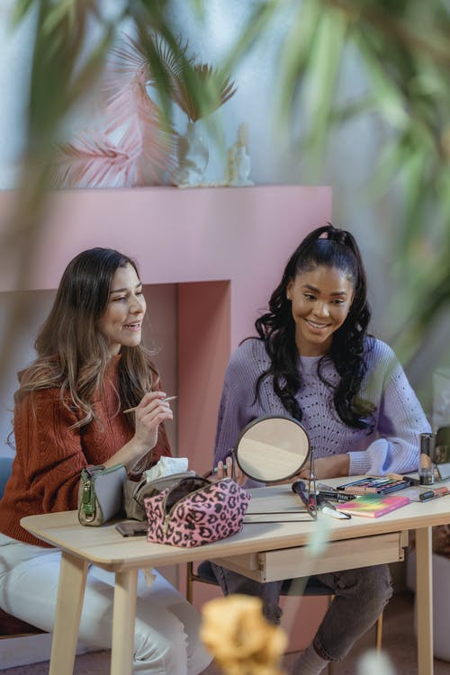 Positive multiethnic female bloggers sitting at table with cosmetic products and mirror and recording vlog on cellphone on tripod
