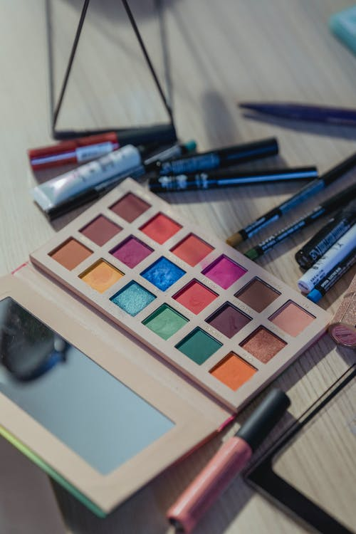 From above of various makeup supplies placed around eyeshadow pallet with mirror on table