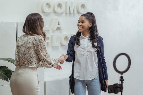 Positive African American female shaking hand of partner standing in light office near smartphone with ring lamp on tripod