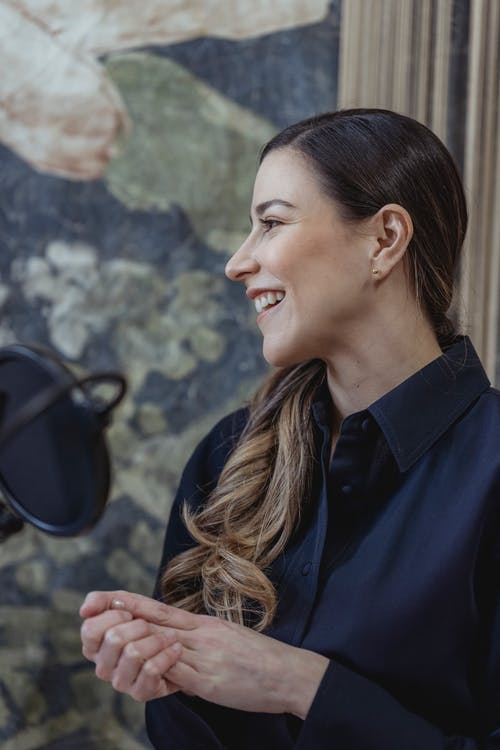 Smiling woman recording podcast on mic