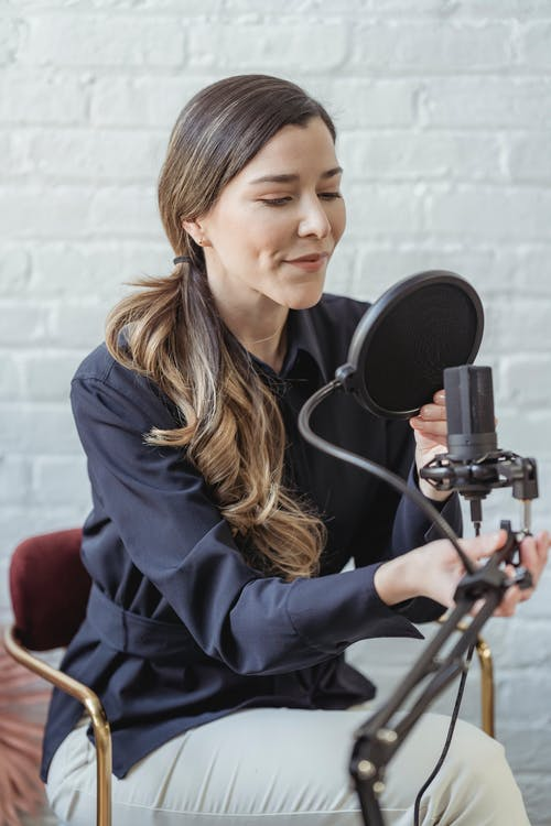 Smiling woman recording voice on microphone