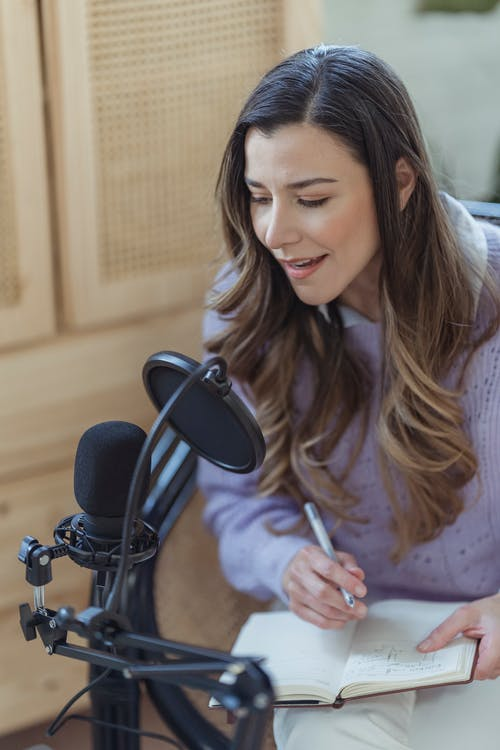 High angle of woman with wavy hair sitting with crossed legs ant talking to mic while working on radio remotely