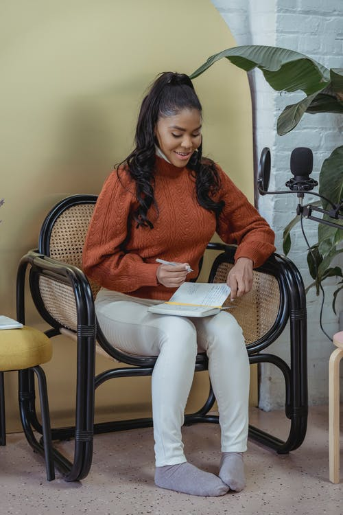 Full body of positive African American female in casual clothes writing in notebook in armchair near potted plant and microphone for recording podcast