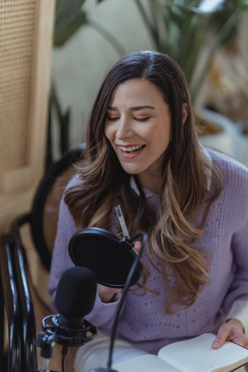 Positive female radio host with professional microphone sitting on chair while recording audio message in light room with green plants