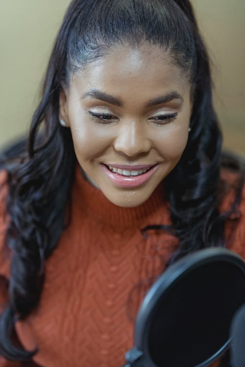 Smiling black woman recording podcast