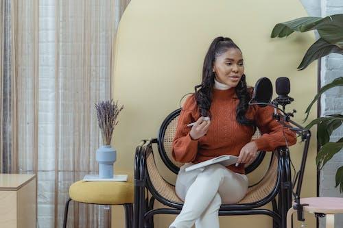 Cheerful black woman recording audio podcast