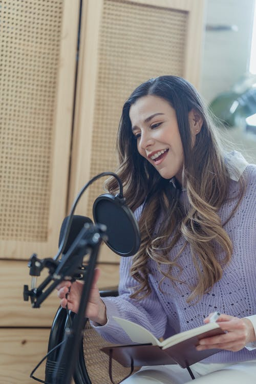 Content female in casual wear talking to professional microphone while recording audio record on chair with opened notebook in light room