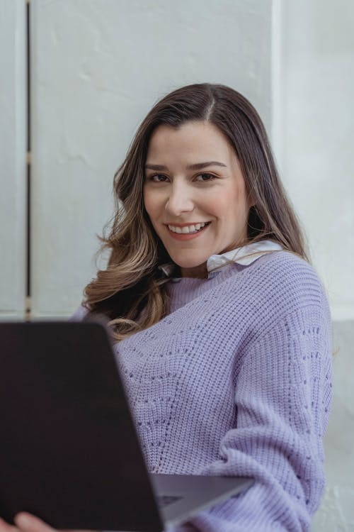 Cheerful woman browsing laptop in room