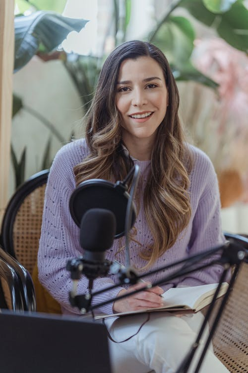 Cheerful female radio host looking at camera while sitting in chair with opened notebook near professional microphone in light room