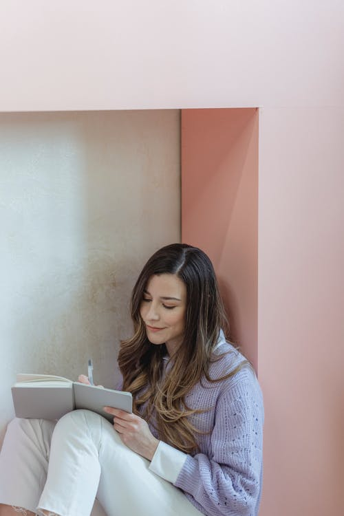 Positive female worker in casual clothes taking notes in notepad while sitting on floor in light room during work assignment